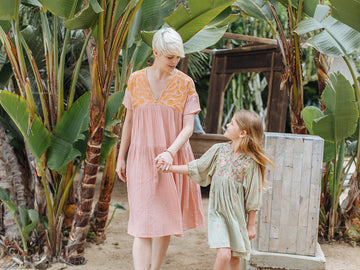Mom and daughter wear their embroidered dresses in the greenery of Encinitas. Click to view the full Women's spring Collection.
