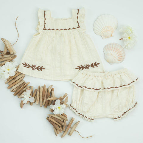 Flat lay of Marabelle 2 piece baby set. Shells and driftwood are used at props to showcase the beach-like feel of the piece.