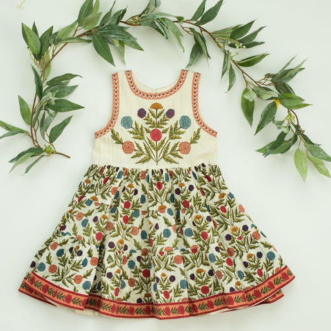 Lenore Dress in multi-gold marigold floral print. Surrounded by greenery.