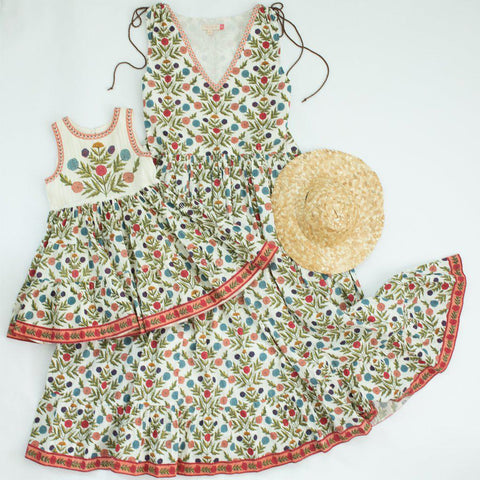 Multi marigold floral dresses - the Lenore dress for girls and the Laurel dress for women paired with a straw hat.
