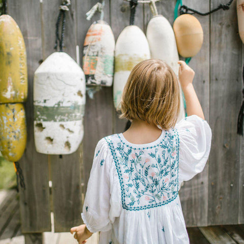 Little girl with back faced to the camera so you can see the unique floral embroidery on the Ava Bella dress.
