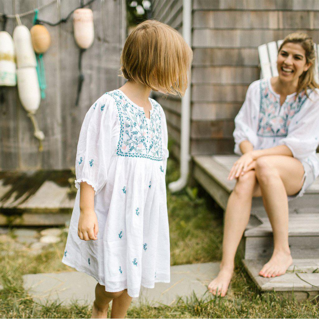 Little girls wear the white Ava Bella dress with blue and pink floral embroidery. She stares back at her smiling mother in a matching Ava Bella top.