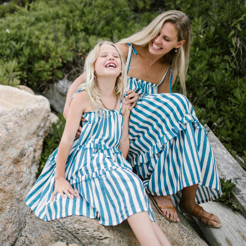 Little girl laughing with mother, both wearing their matching Garden dresses in blue and white striped combo.