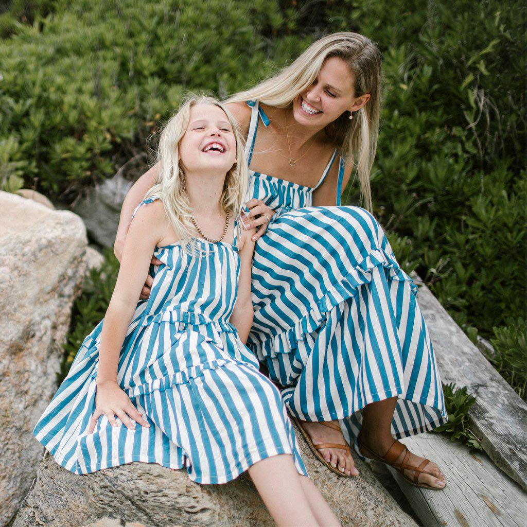 Mother and daughter laughing while wearing their matching Garden dresses in blue and white stripes.