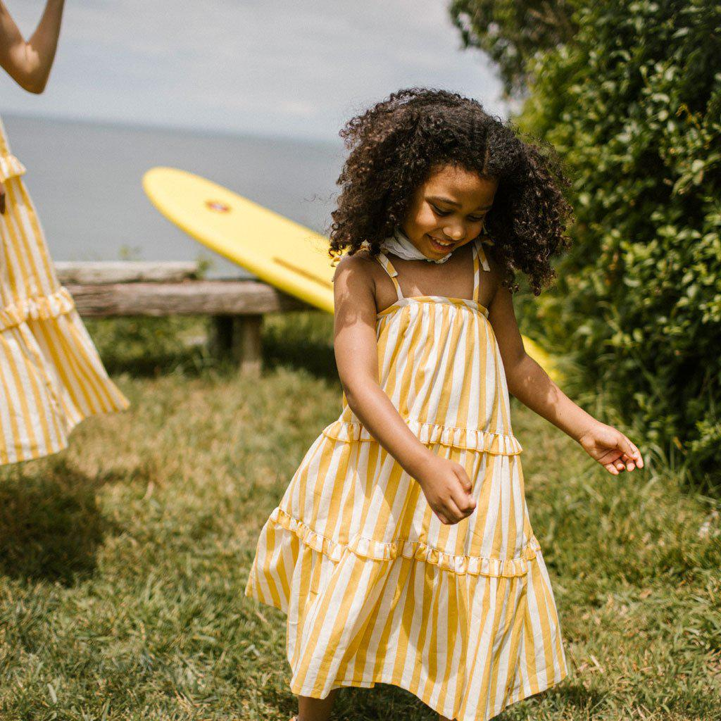 Young girl with brown hair walks along the grass in her yellow and white striped Garden Dress.