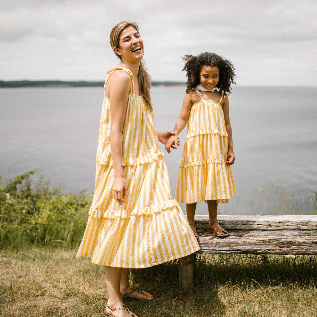 Mother and daughter wearing matching yellow and white striped Garden dresses near the water.