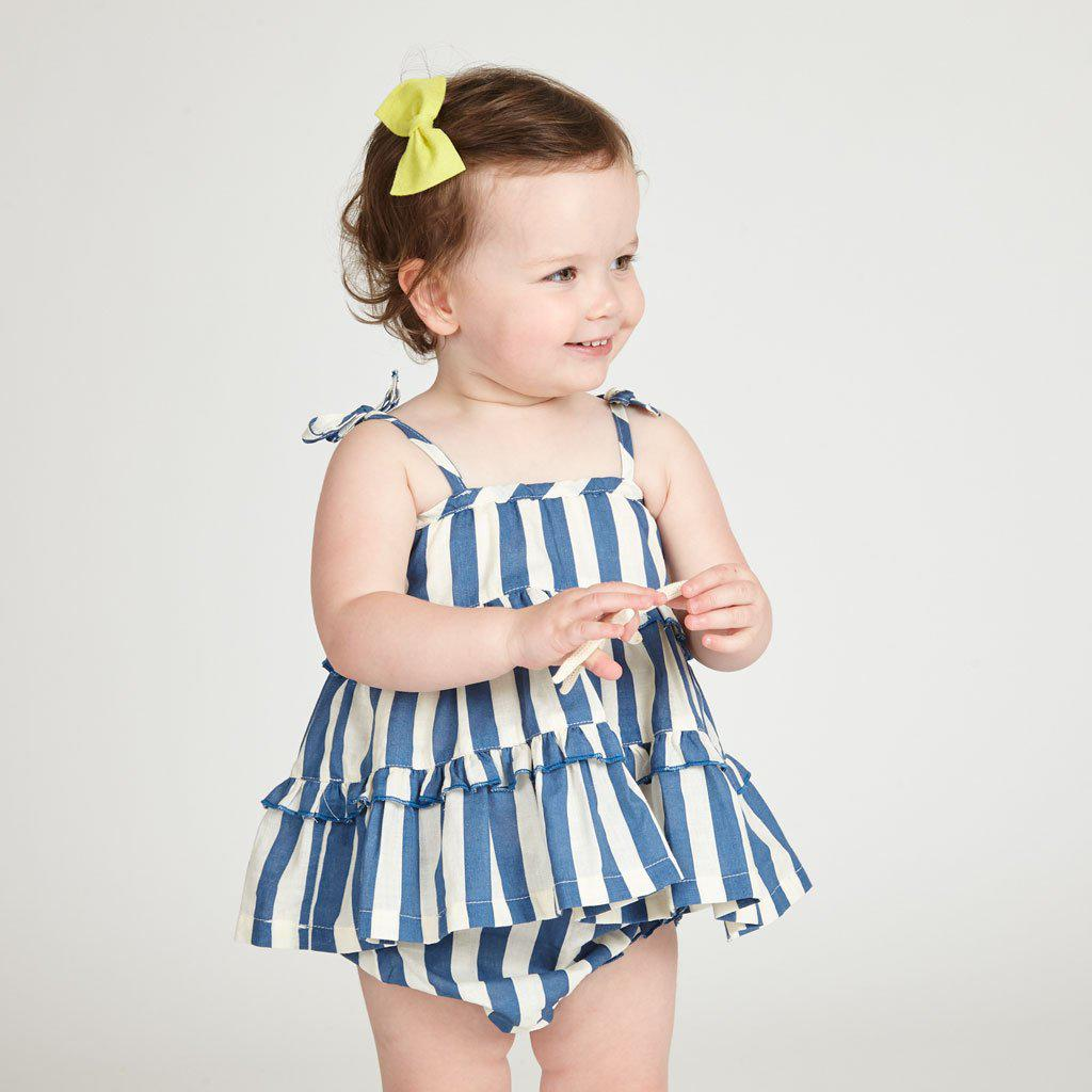 Smiling baby girl wearing Baby Garden 2-piece set in dress blues stripe/white with yellow bow in hair.