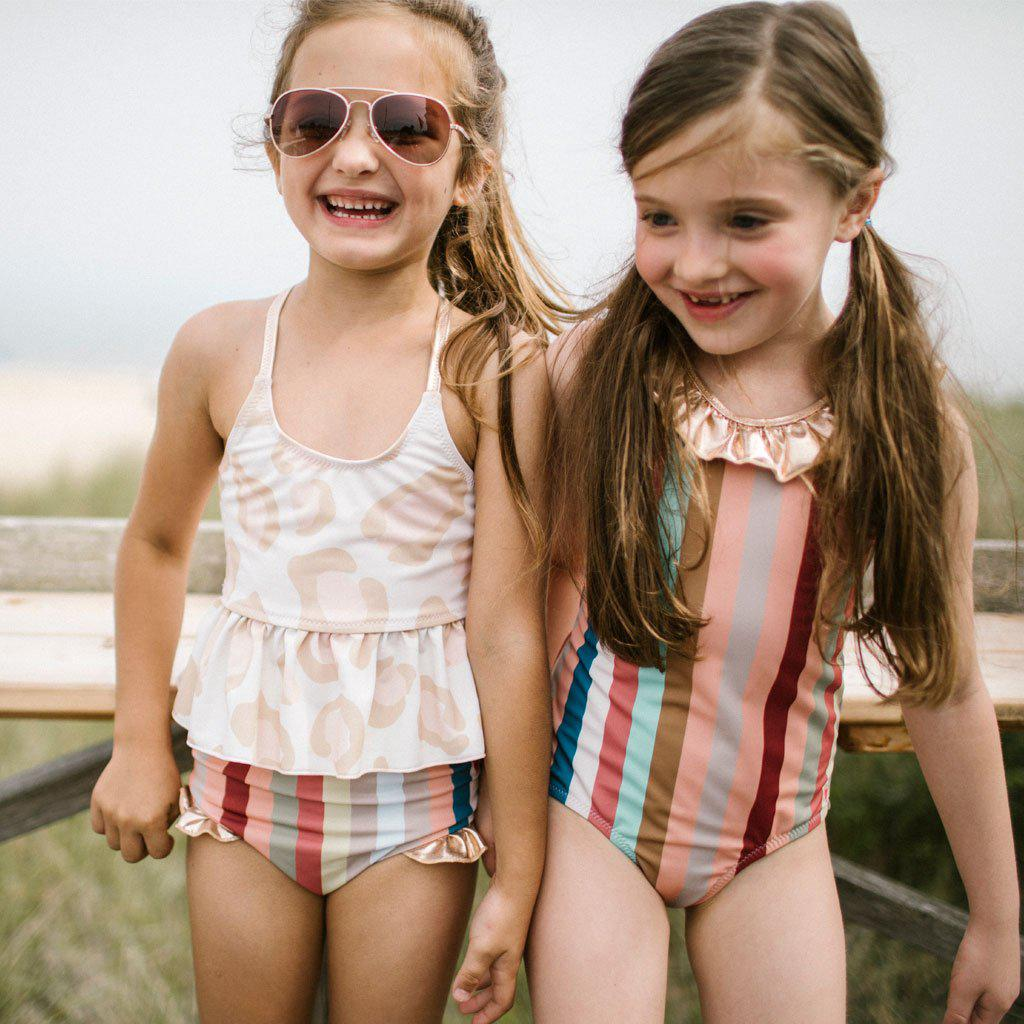 Two girls in Pink Chicken bathing suits - Joy Tankini in antique white oversized leopard and Princess Diana Suit in multi vintage stripe