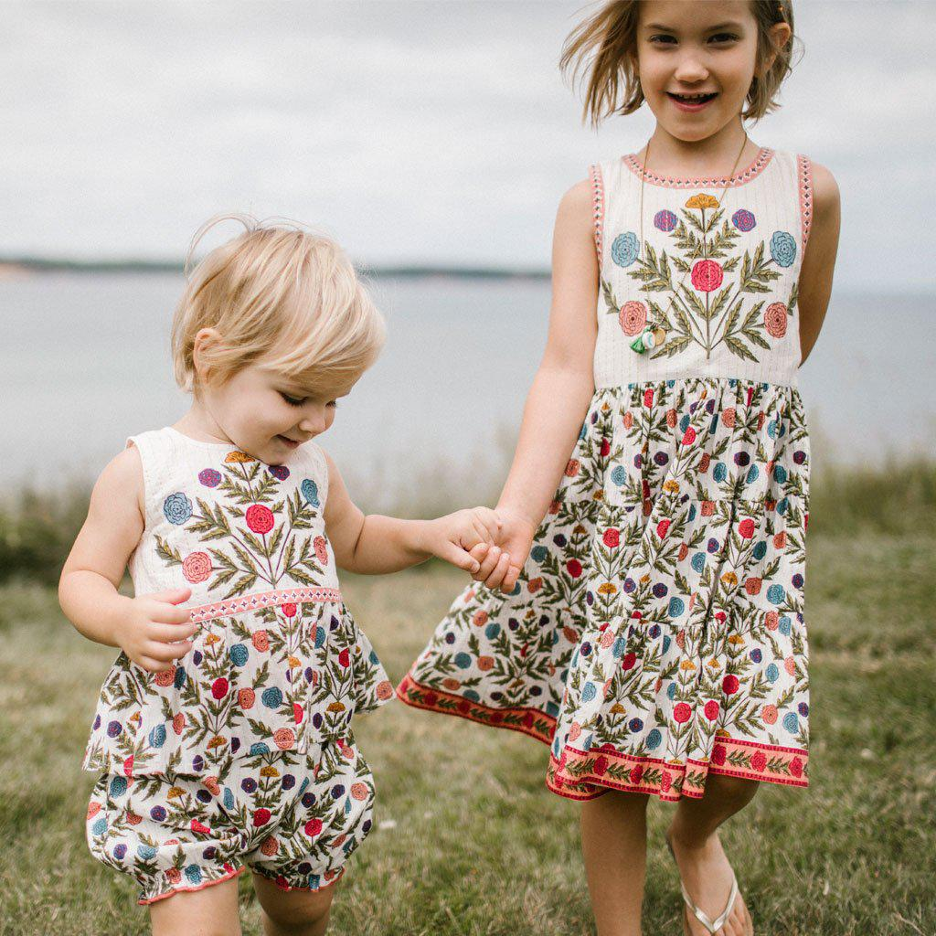 Baby girl and little girl model stand beside the water holding hands in their matching outfits. Libby 2 piece set for baby and the Lenore Dress for little girl. Both with multi-marigold patterns.