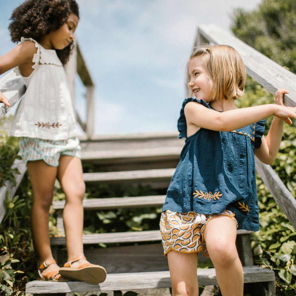 2 Young girls walking down stairs wearing the blue Marabelle top and the white Marabelle top.