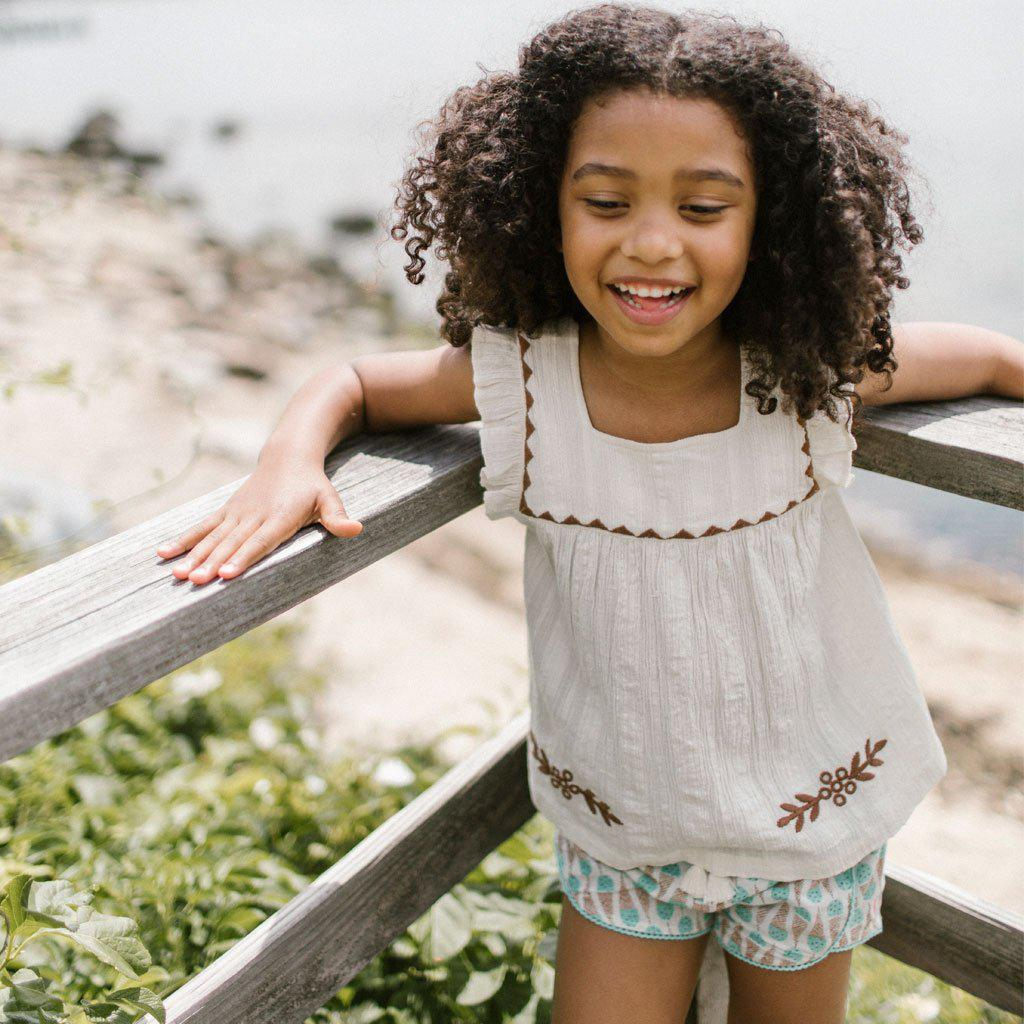 Young girl wears the Marabelle top in antique white with neutral floral embroidery.