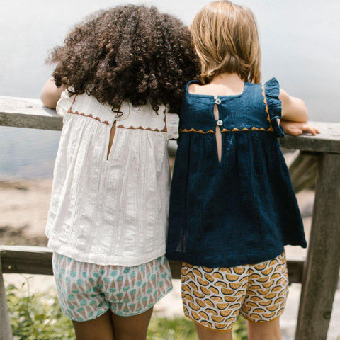 Two young girls stand next to each other facing the water. Wearing Marabelle tops in antique white and dress blues.