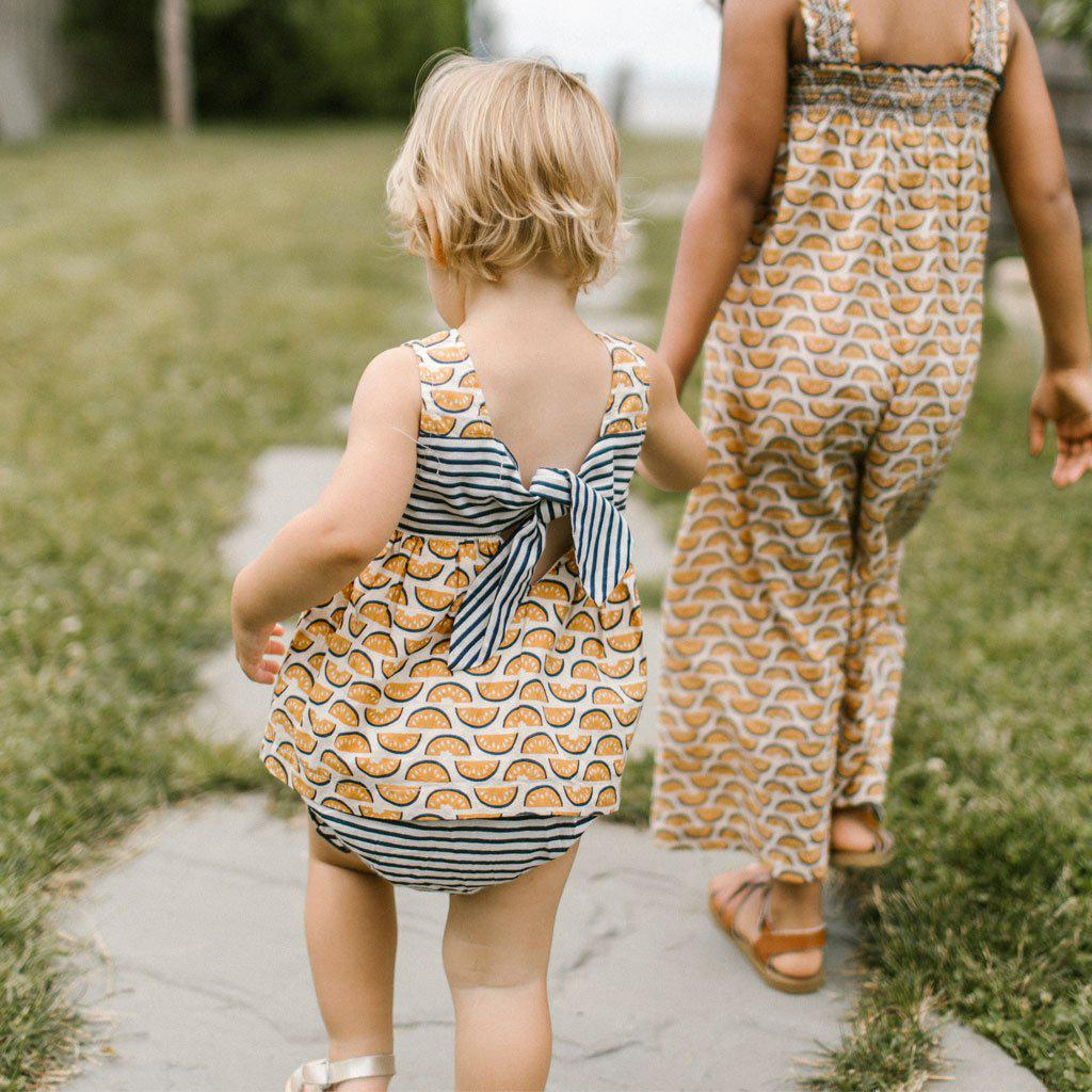 Baby girl holds hands with her sister as she walks through the grass, showcasing her adorable bow on the back of her River 2 piece watermelon and striped set.