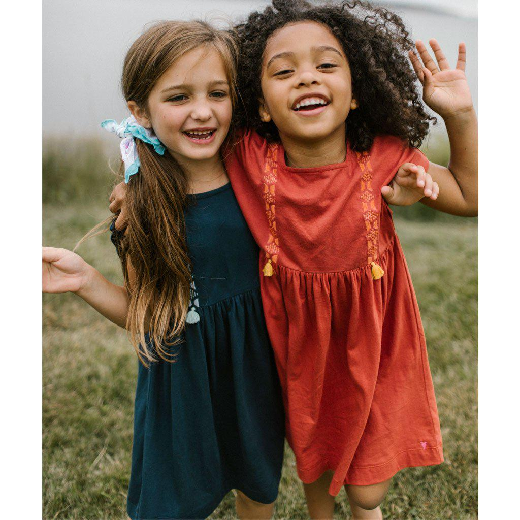 Two little girls waving hello in their Stacey dresses. One in the tandoori spice color and the other in the dress blues color.