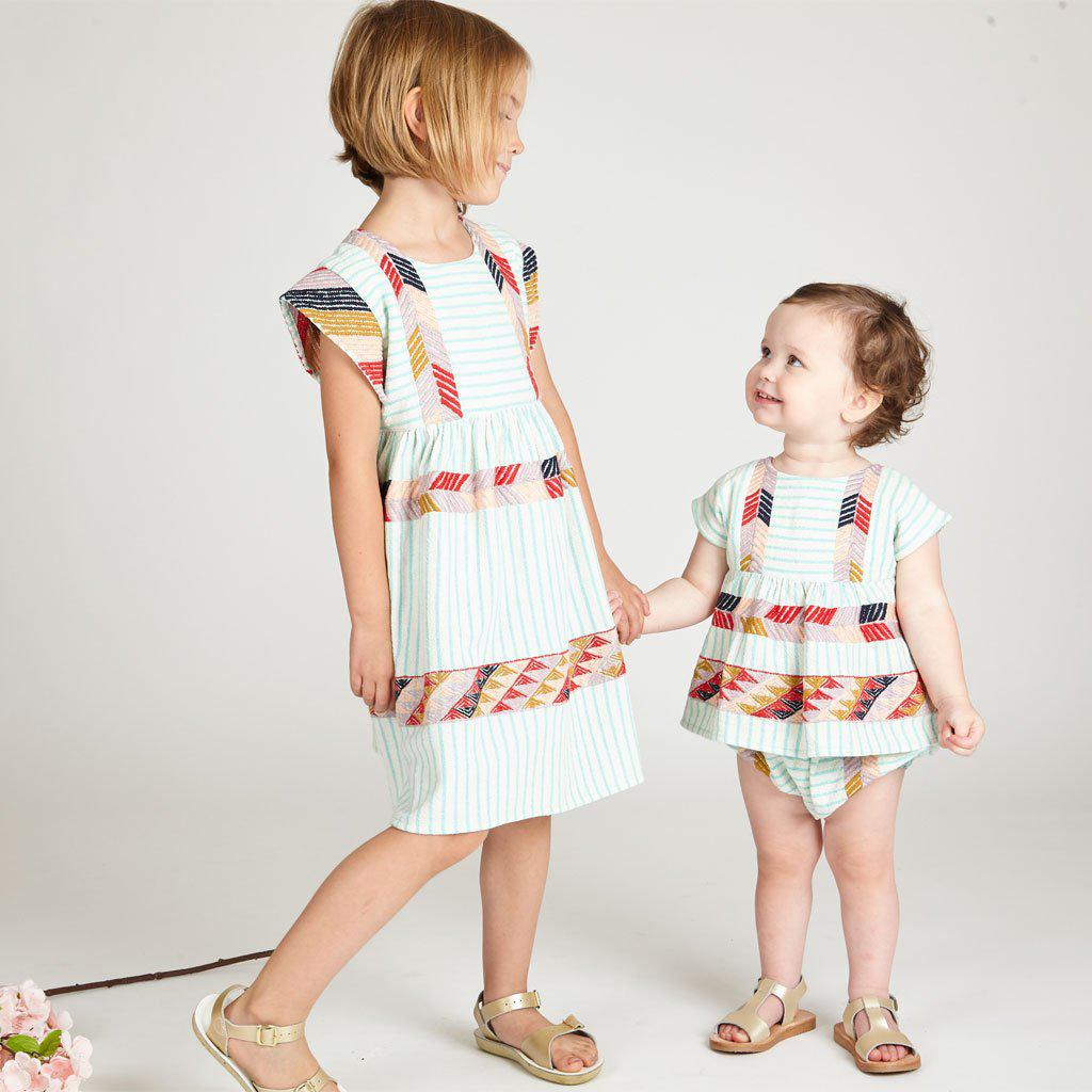 Little girl wearing the Suri Dress with pool blue stripe with multi colored peru embroidery. Baby sister holding her hand wearing a 2 piece set with same print.