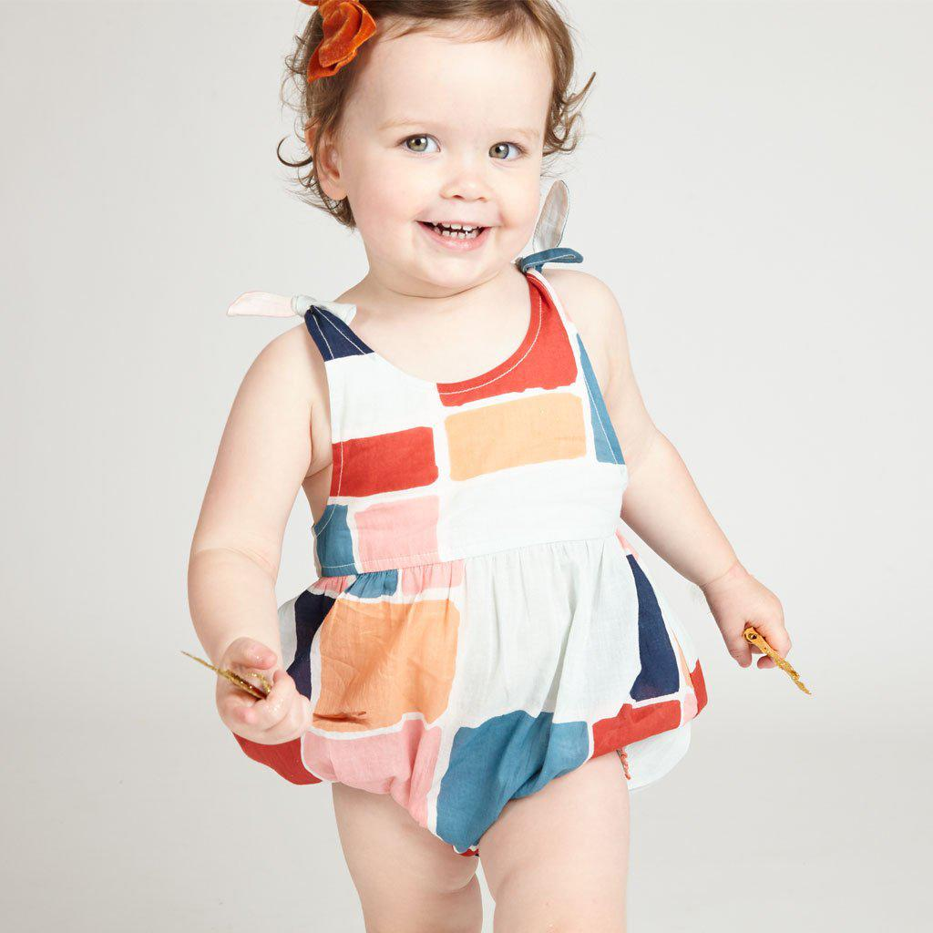 Smiling baby girl wearing the Taylor bubble with multi-print squares print.