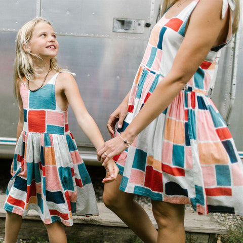 Little girl holds hands with mom, both in matching printed Taylor dresses - multi paint square.