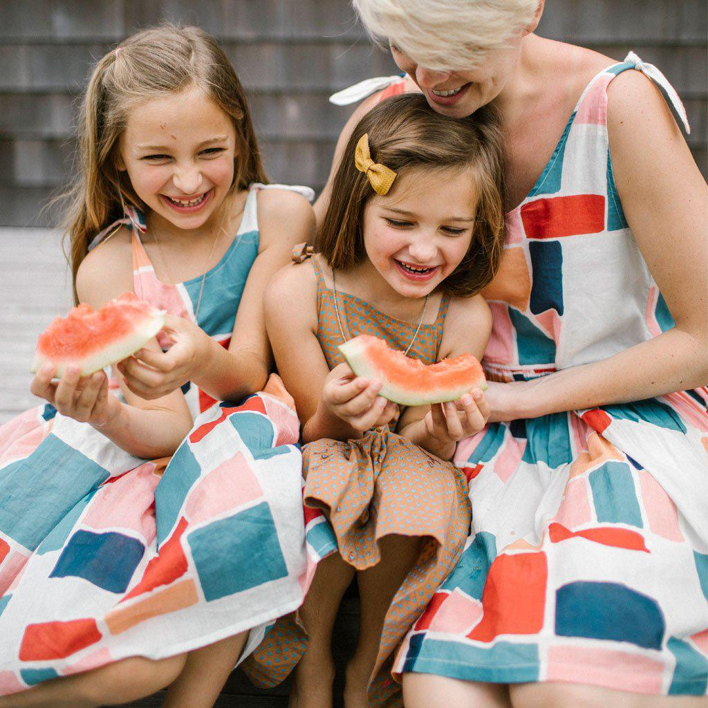 Little girls and mom laughing and eating watermelon, wearing their matching Taylor dresses in multi paint square print.
