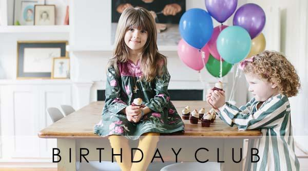 Girl sitting on a dining room table with her sister next to her holding a bunch of balloons. Cupcakes are on the table. Join the Pink Chicken Birthday Club!