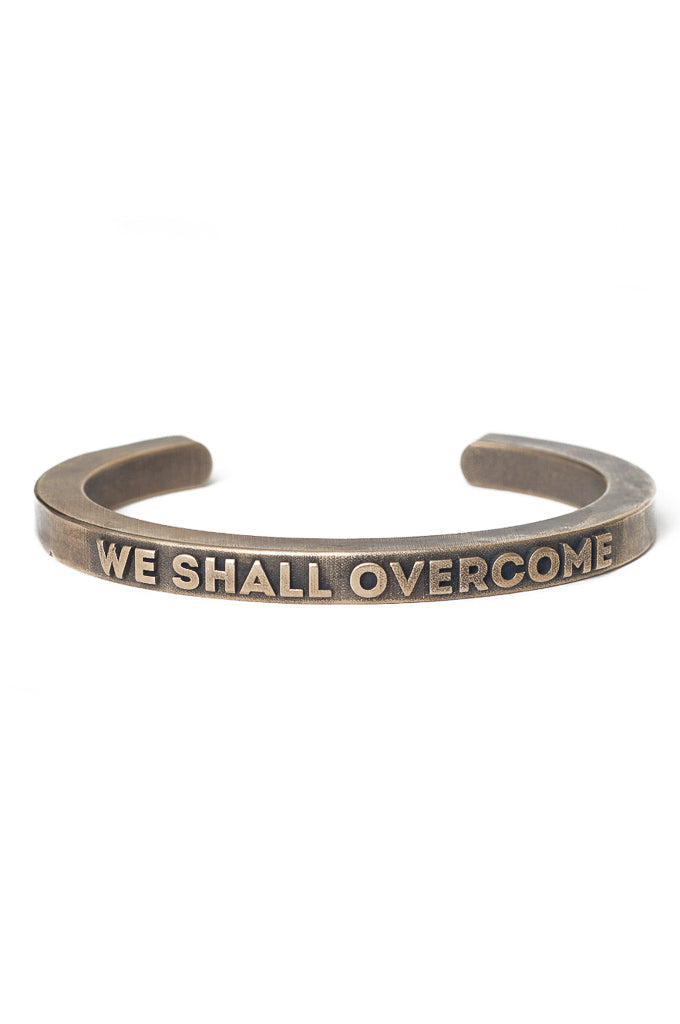 We shall overcome cuff in polished brass. Thick cuff that reads