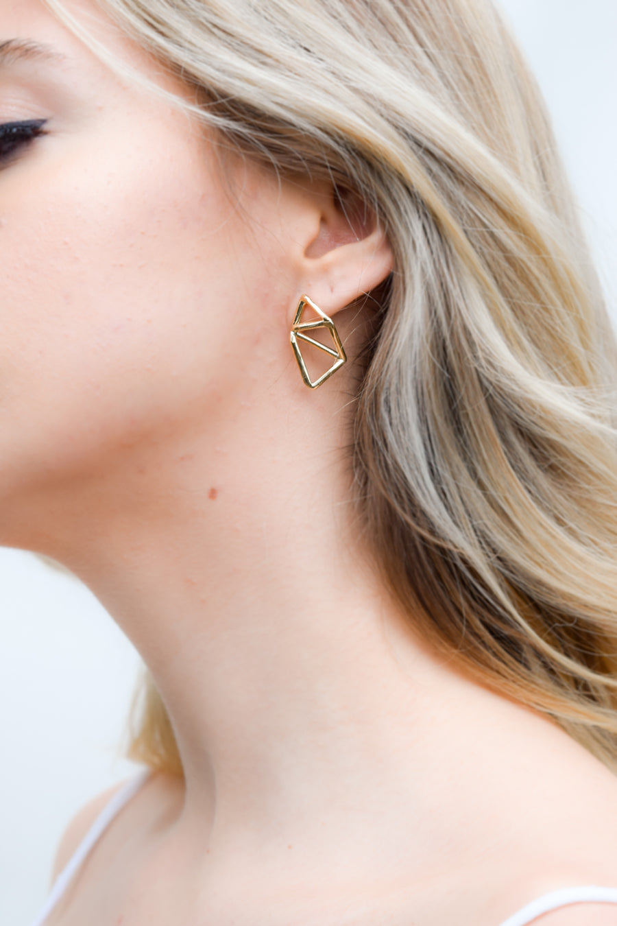 Bichito earring on model. 14k yellow gold uniquely asymmetrical earrings. Handmade by local jewelry designer, Nina Berenato, in Austin, Texas.