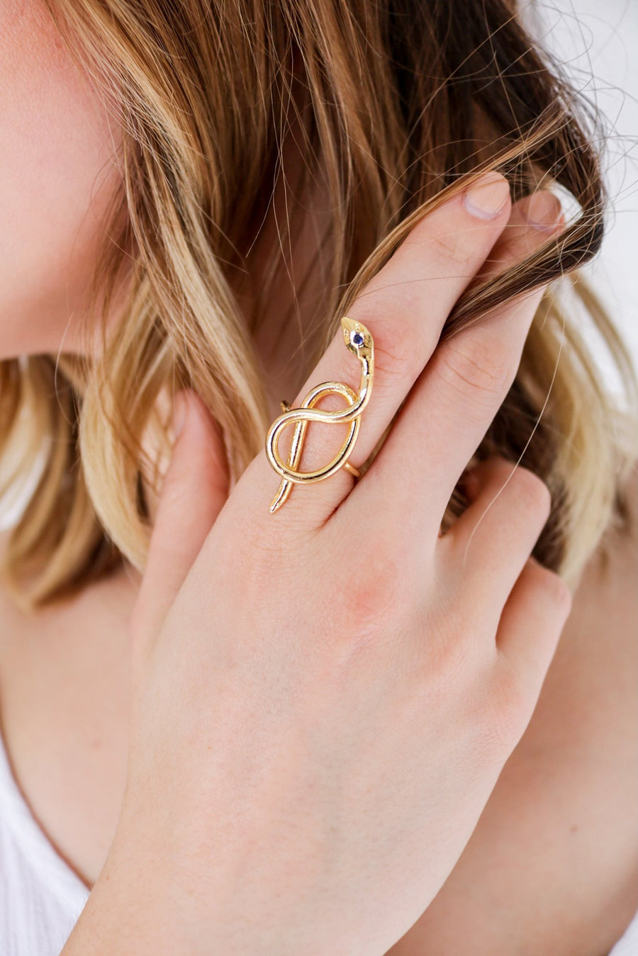 Coiled serpent snake ring on model. 14k yellow gold hand carved snake ring set with a birthstone in the head. Handmade by local jewelry designer, Nina Berenato, in Austin, Texas.