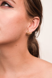 Inferno earring on model. 14k yellow gold earring that tucks underneath and hugs the lobe of the ear. Handmade by local jewelry designer, Nina Berenato, in Austin, Texas.