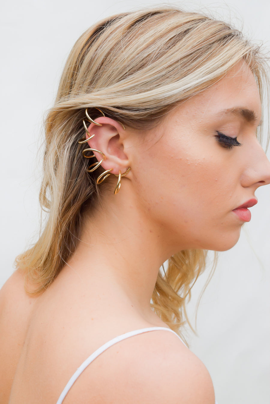 Rebel ear cuff on model. 14k yellow gold one-sided ear cuff with multiple large coil design. No piercing required. Handmade by local jewelry designer, Nina Berenato, in Austin, Texas.