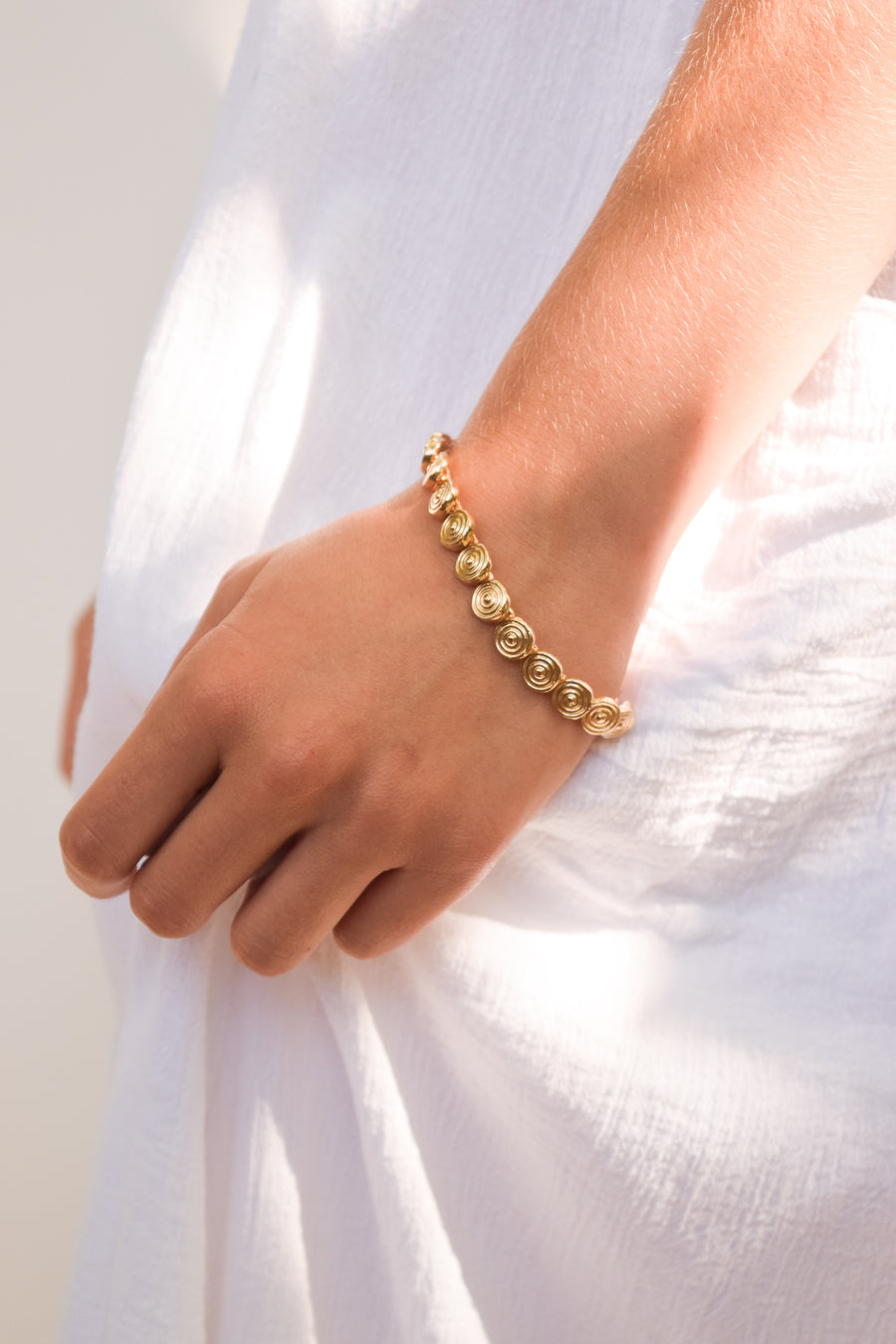 Abundance tennis bracelet on model. 14k yellow gold bracelet linked together with circle designs and is 7.5 inches. Handmade by local jewelry designer, Nina Berenato, in Austin, Texas.