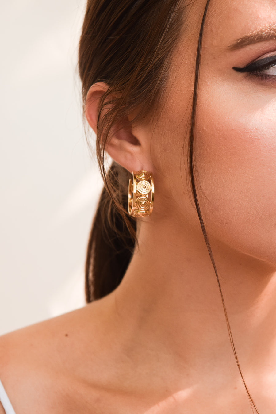 Aluna mini hoop earrings on model. 14k yellow gold hoops with circular design and are 1 inch in diameter. Handmade by local jewelry designer, Nina Berenato, in Austin, Texas.