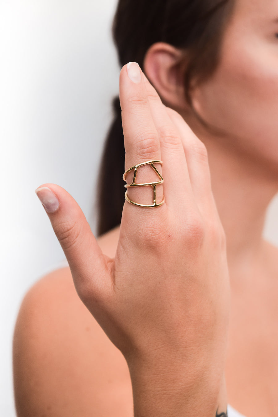 Fragment ring on model. 14k yellow gold ring with an asymmetrical design. Handmade by local jewelry designer, Nina Berenato, in Austin, Texas.