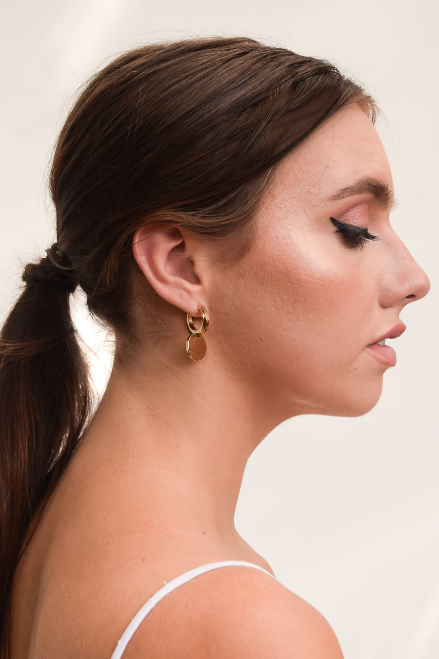 Cycle earring on model. 14k yellow gold earring with a modern circular design. Handmade by local jewelry designer, Nina Berenato, in Austin, Texas.