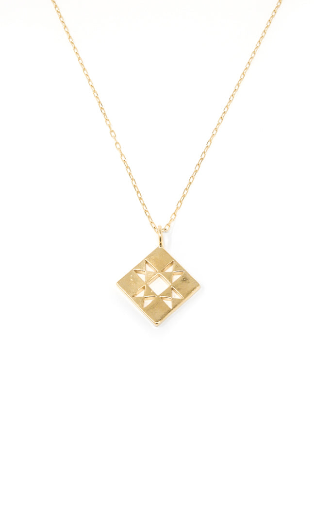 Quilt charm necklace in 14k yellow gold. Necklace with small quilt patchwork charm on a 16 inch chain. Handmade by local jewelry designer, Nina Berenato, in Austin, Texas.
