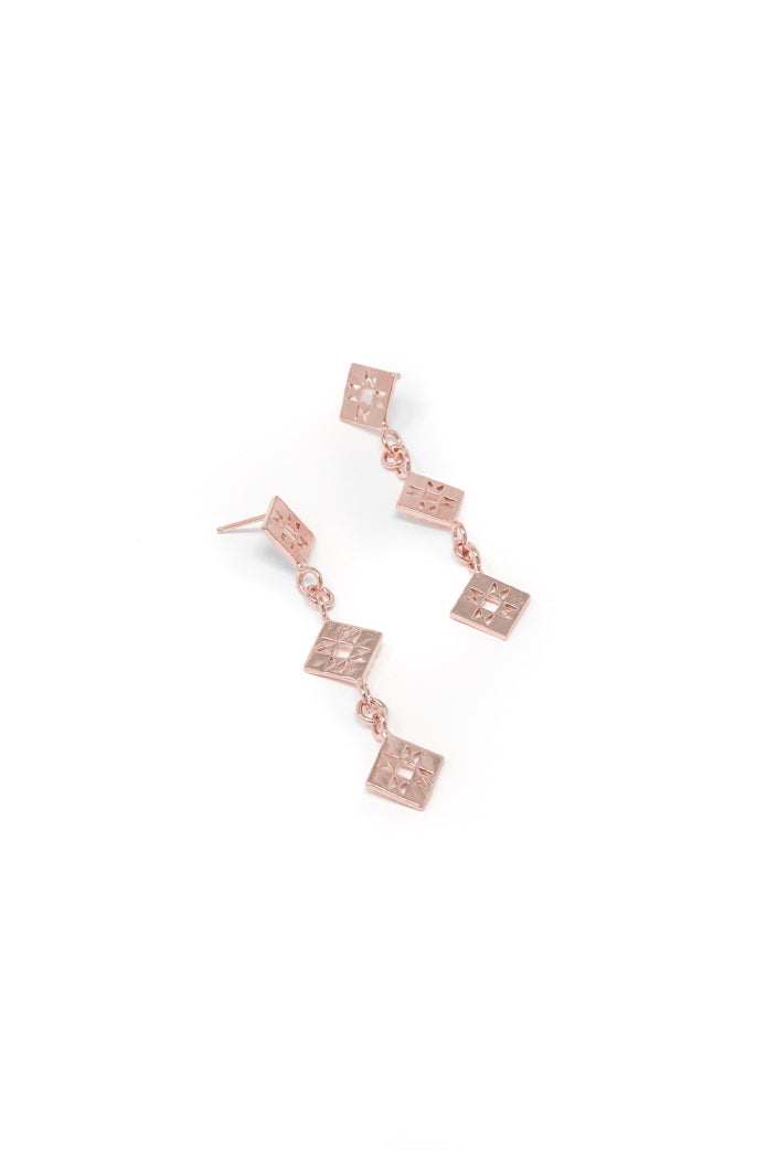 Small quilt dangle earring in 14k rose gold. Dangle earrings with quilt patchwork designs linked together for movement. 2.5 inches in length. Handmade by local jewelry designer, Nina Berenato, in Austin, Texas.