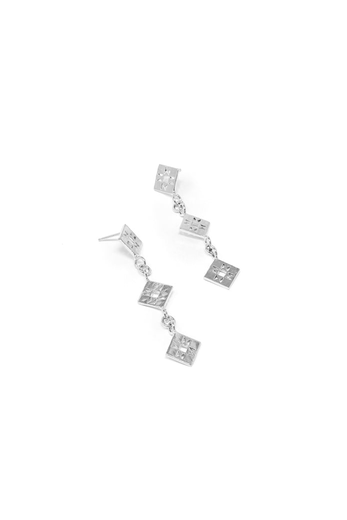 Small quilt dangle earring in 14k white gold. Dangle earrings with quilt patchwork designs linked together for movement. 2.5 inches in length. Handmade by local jewelry designer, Nina Berenato, in Austin, Texas.