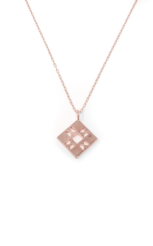 Quilt charm necklace in 14k rose gold. Necklace with small quilt patchwork charm on a 16 inch chain. Handmade by local jewelry designer, Nina Berenato, in Austin, Texas.