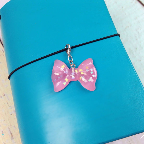 Light pink resin bow charm with iridescent stars inside hanging on a Ocean Springs blue Delta Travelers Notebook