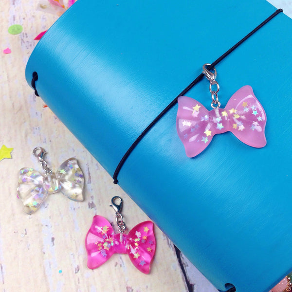 Resin bow charms with iridescent stars inside hanging on a Ocean Springs blue Delta Travelers Notebook
