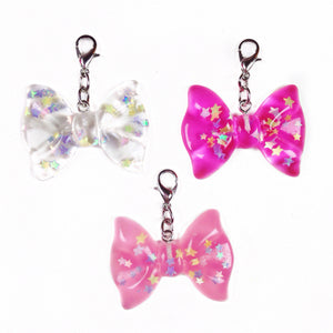 Resin bow charms with iridescent stars inside that are perfect for travelers notebooks