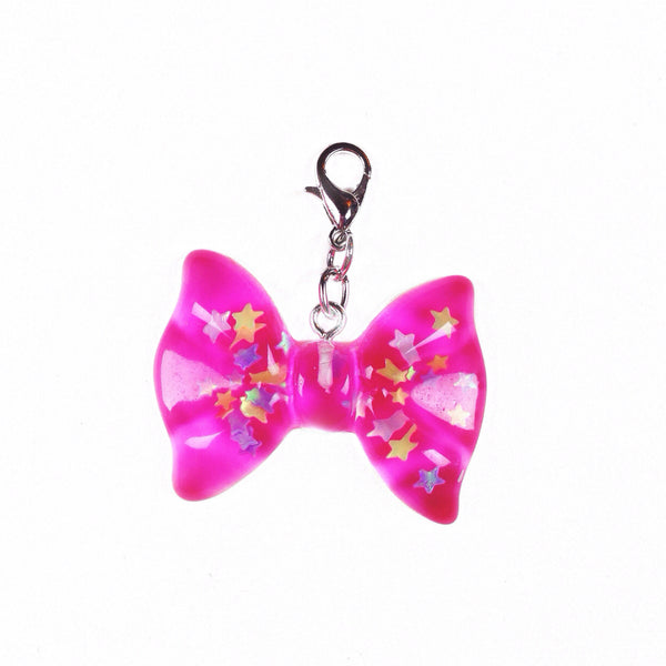 Dark pink resin bow charm with iridescent stars inside perfect for travelers notebooks