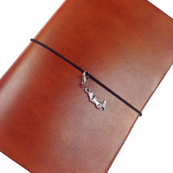 Silver mermaid charm on lobster clasp hanging on a leather Delta Travelers notebook