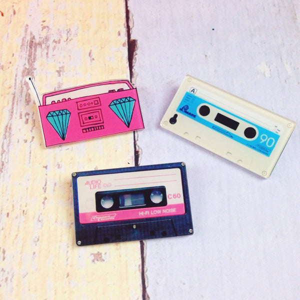 Three flair pins – a pink boombox, a black cassette tape, and a white cassette tape – on a wood patterned background.