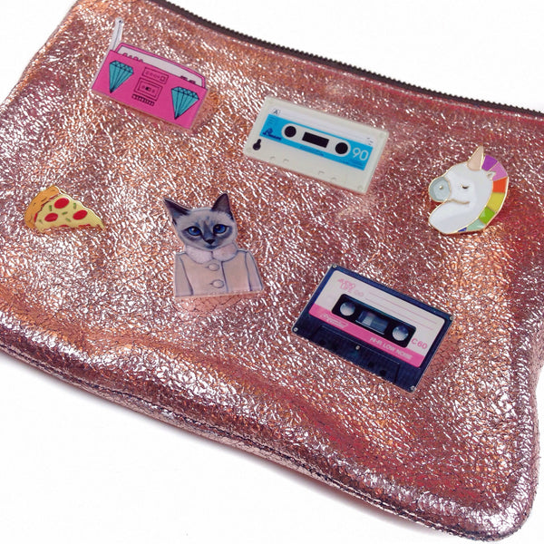 Various kawaii flair pins on a sparkly clutch