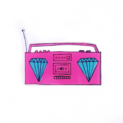 A pink boombox flair pin with diamonds for speakers and an antenna