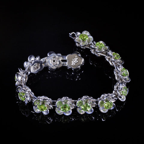 Sterling silver flower blossom bracelet featuring peridots and a white gold clasp