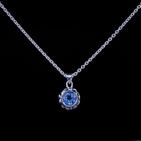 A sterling silver bezel set gemstone pendant featuring a blue topaz.