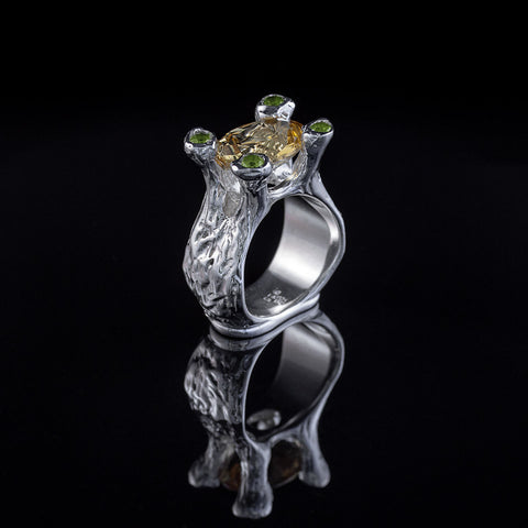 Amphora Ring with garnet center stone, peridot set prongs and diamond pave on bottom
