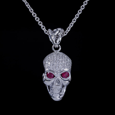 Skull pendant in 14k white gold with ruby eyes and diamond pave