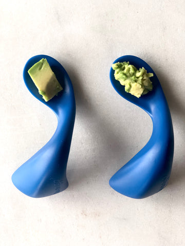 two blue curved spoons with mashed and diced avocado
