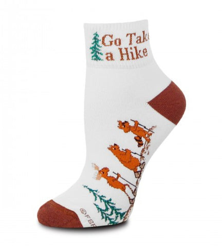 On an Anklet Style Sock FBF Go Take a Hike is on the Cuff. The Heels and Toes are Dark Brown and the Moose Bear and Raccoon are Light Brown wearing Boot Hiking in the Forest of Green Pines.